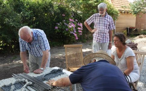 Het maken van een trammelantmat tijdens Demonstratie Ambachten in de tuin van het museumie